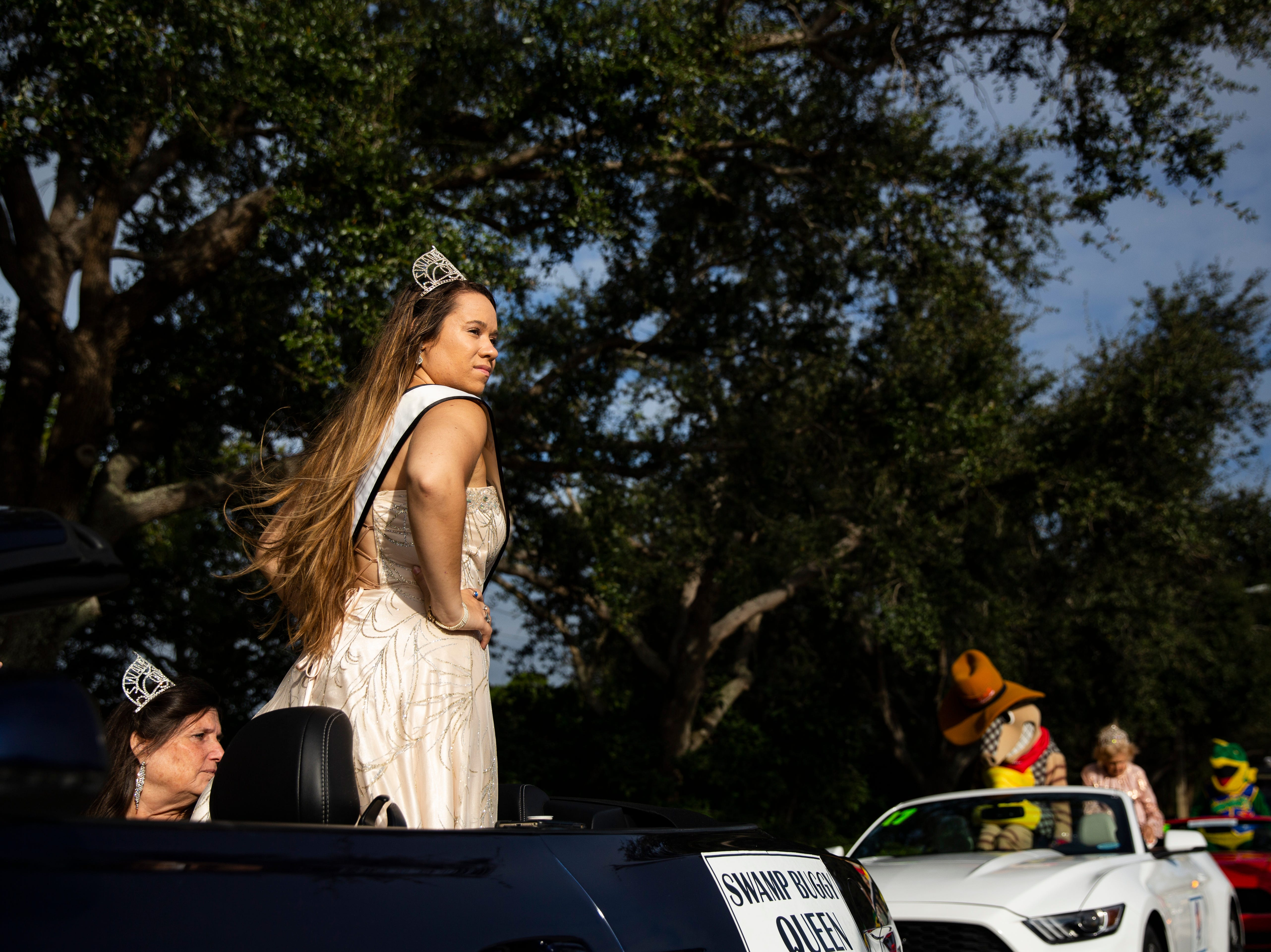 Erica Flesher, 23, wears a glittery pageant-style dress during the 70th annual Swamp Buggy Parade Saturday morning, Nov. 3, 2018. She's served as Swamp Buggy queen the past four years. Saturday's parade featured past Swamp Buggy Queens, Naples High School marching band, racing buggies and Swampy - the race mascot, among other things.