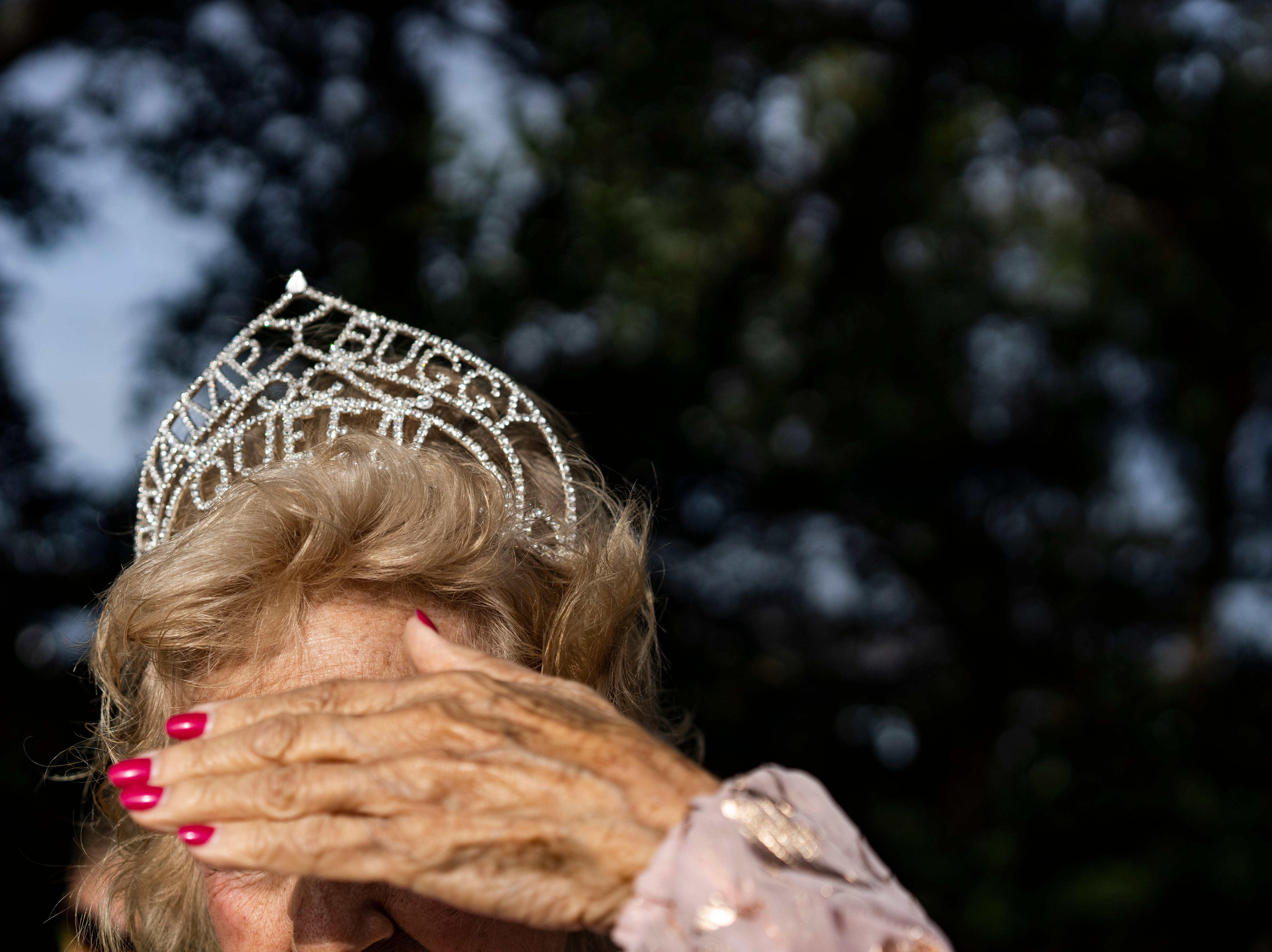 Dolly Scott, 83, covers her eyes from the sun's glare while waiting for the 70th annual Swamp Buggy Parade to start Saturday morning, Nov. 3, 2018. She was crowned Swamp Buggy Queen in 1966. She's one of nearly 70 queens part of swamp buggy history. Saturday's parade featured past Swamp Buggy Queens, Naples High School marching band, racing buggies and Swampy - the race mascot, among other things.