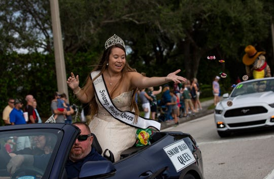 Erica Flesher, 23, throws candy and wooden coins during the 70th annual Swamp Buggy Parade Saturday morning, Nov. 3, 2018. She's served as Swamp Buggy queen the past four years. Saturday's parade featured past Swamp Buggy Queens, Naples High School marching band, racing buggies and Swampy - the race mascot, among other things.