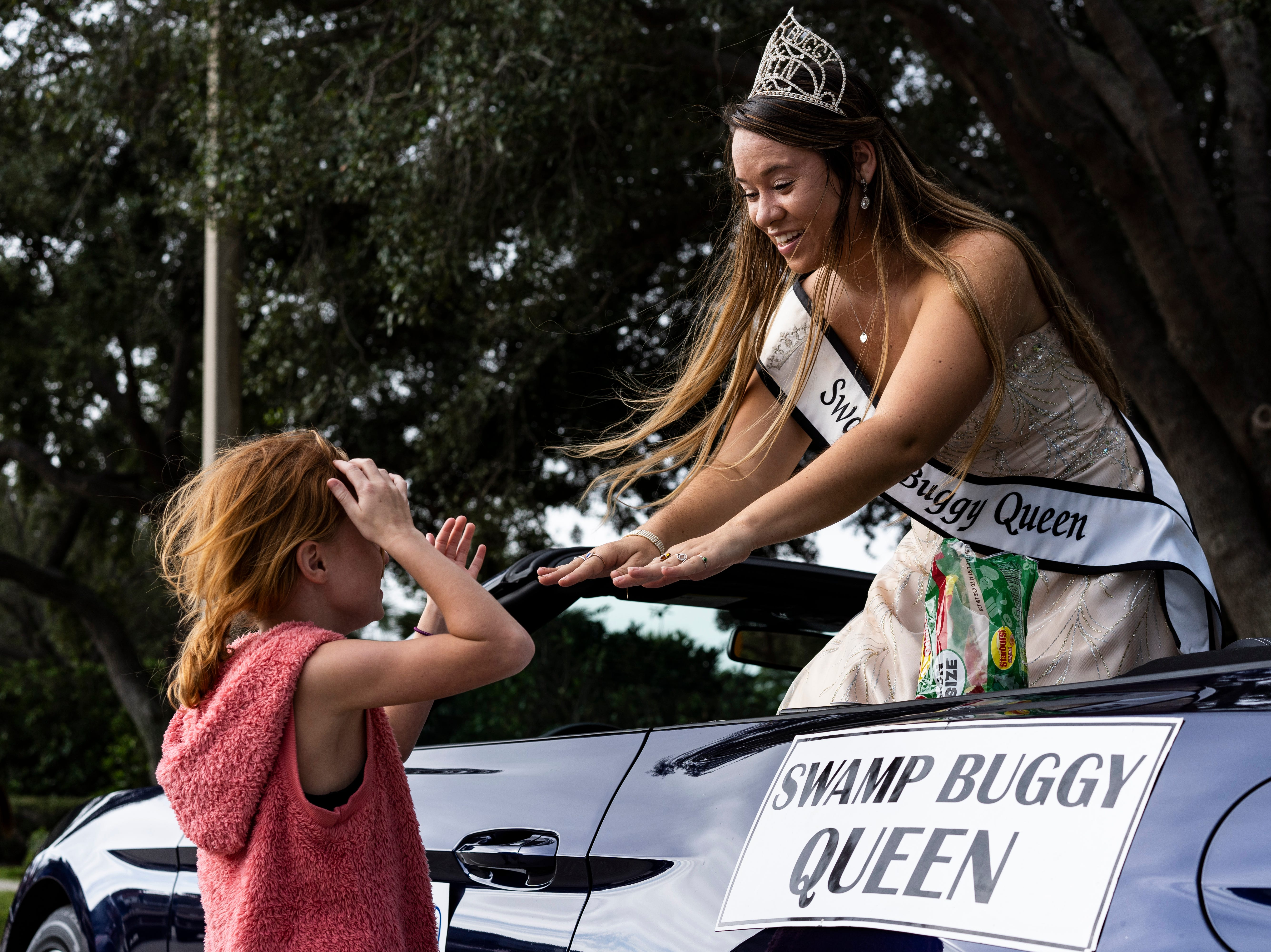 Current Swamp Buggy Queen Erica Flesher, 23, plays a game with Peyton Widner, 7, before the kick-off of the 70th annual Swamp Buggy Parade Saturday morning, Nov. 3, 2018. She's served as Swamp Buggy queen the past four years. Saturday's parade featured past Swamp Buggy Queens, Naples High School marching band, racing buggies and Swampy - the race mascot, among other things.