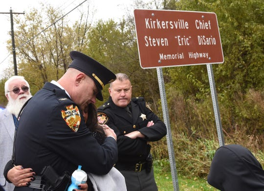 Newark Police Chief Barry Connell hugs Aryn DiSario, widow of former Kirkersville Police Chief Steven Eric DiSario, after a ceremony to rename the section of U.S. 40 that runs through the village of KirkersvilleÊin memory of her husband.