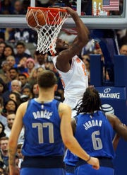 New York Knicks center Mitchell Robinson (26) lands a dunk against Dallas Mavericks forward Luka Doncic (77) and center DeAndre Jordan (6) in the second half of an NBA basketball game Friday, Nov. 2, 2018, in Dallas.