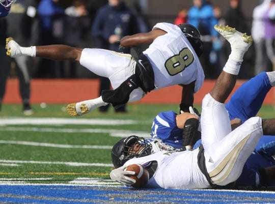 Andy Ambroise jumps over team mate David Stevens of Paramus Catholic after Stevens was tackled in the second half.
