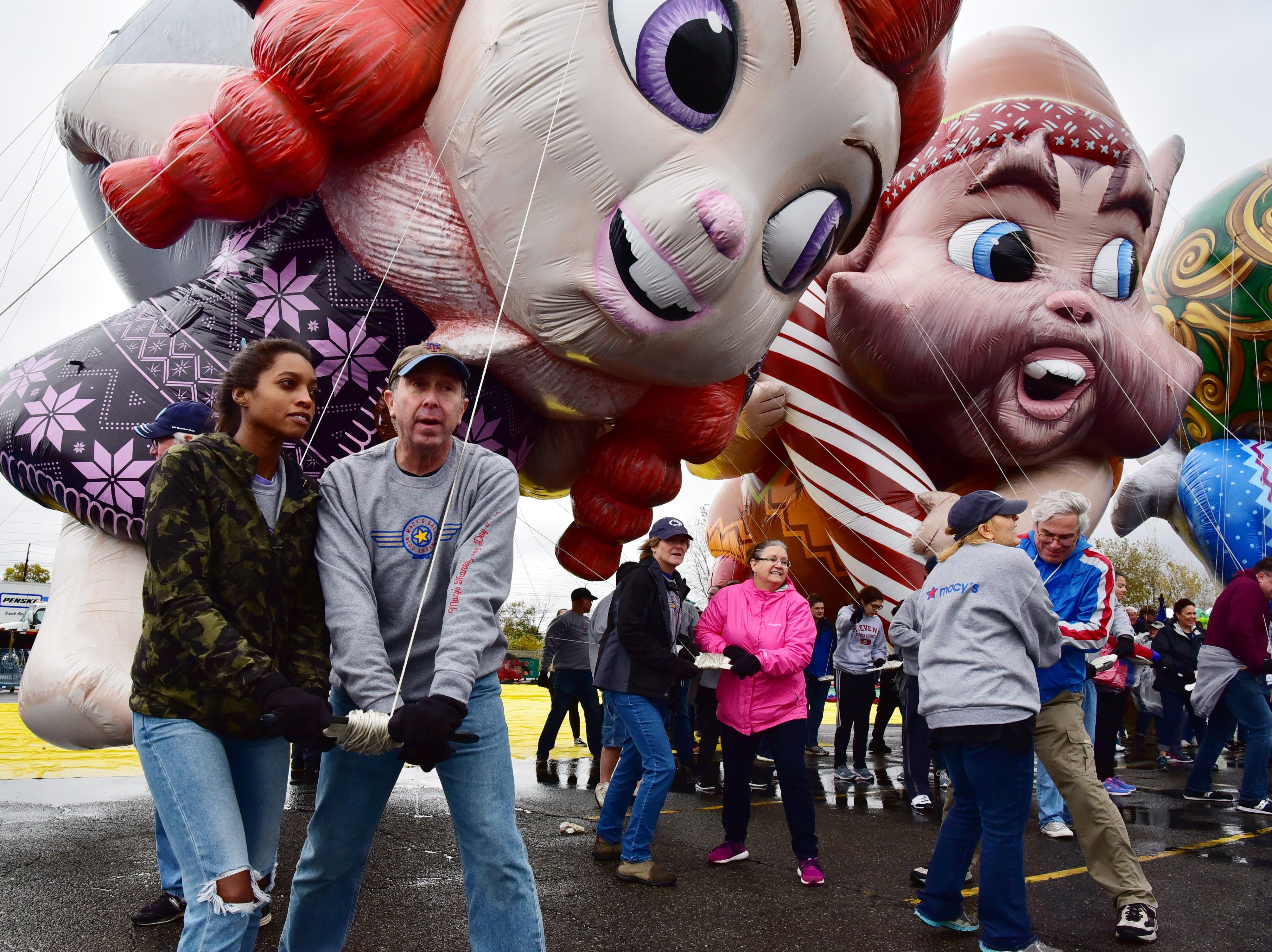 Volunteers Zuki Wilson and Steve Simon, test fly Fleck, Bjorn and Jojo, the newest Macy's Thanksgiving Parade balloons, at MetLife Stadium parking lot on Saturday, November 3.