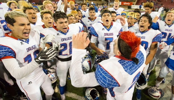 Las Cruces High School football players celebrate after winning the annual Cruces/Mayfield football game on Friday, Nov. 2, 2018, at Aggie Memorial Stadium.