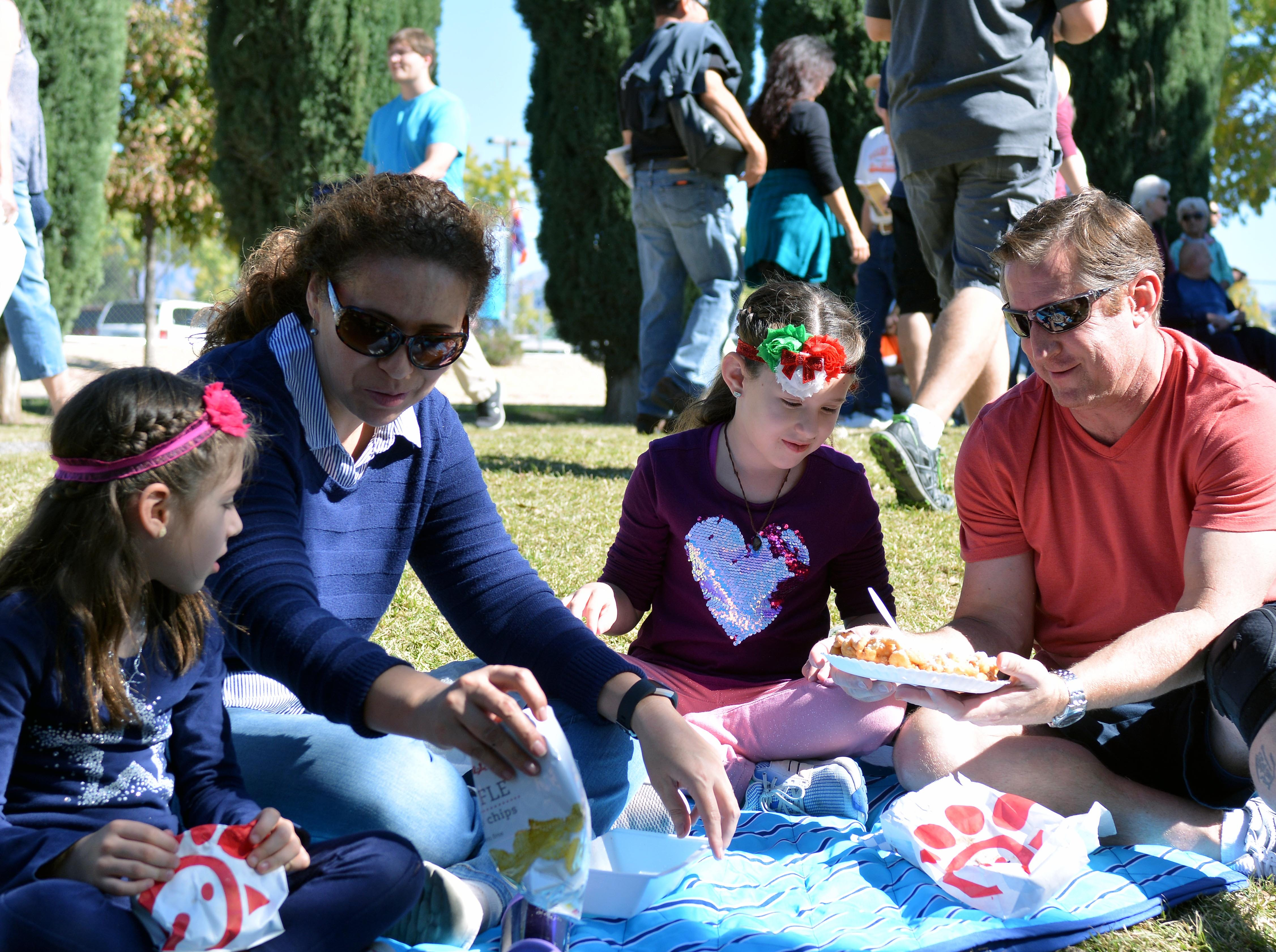 The Haubner family (left to right: Marissa, Elizabeth, Arianna and Ken) from Las Cruces take in the sun and enjoy a funnel cake on Saturday afternoon.  Photo taken 11/3/18.