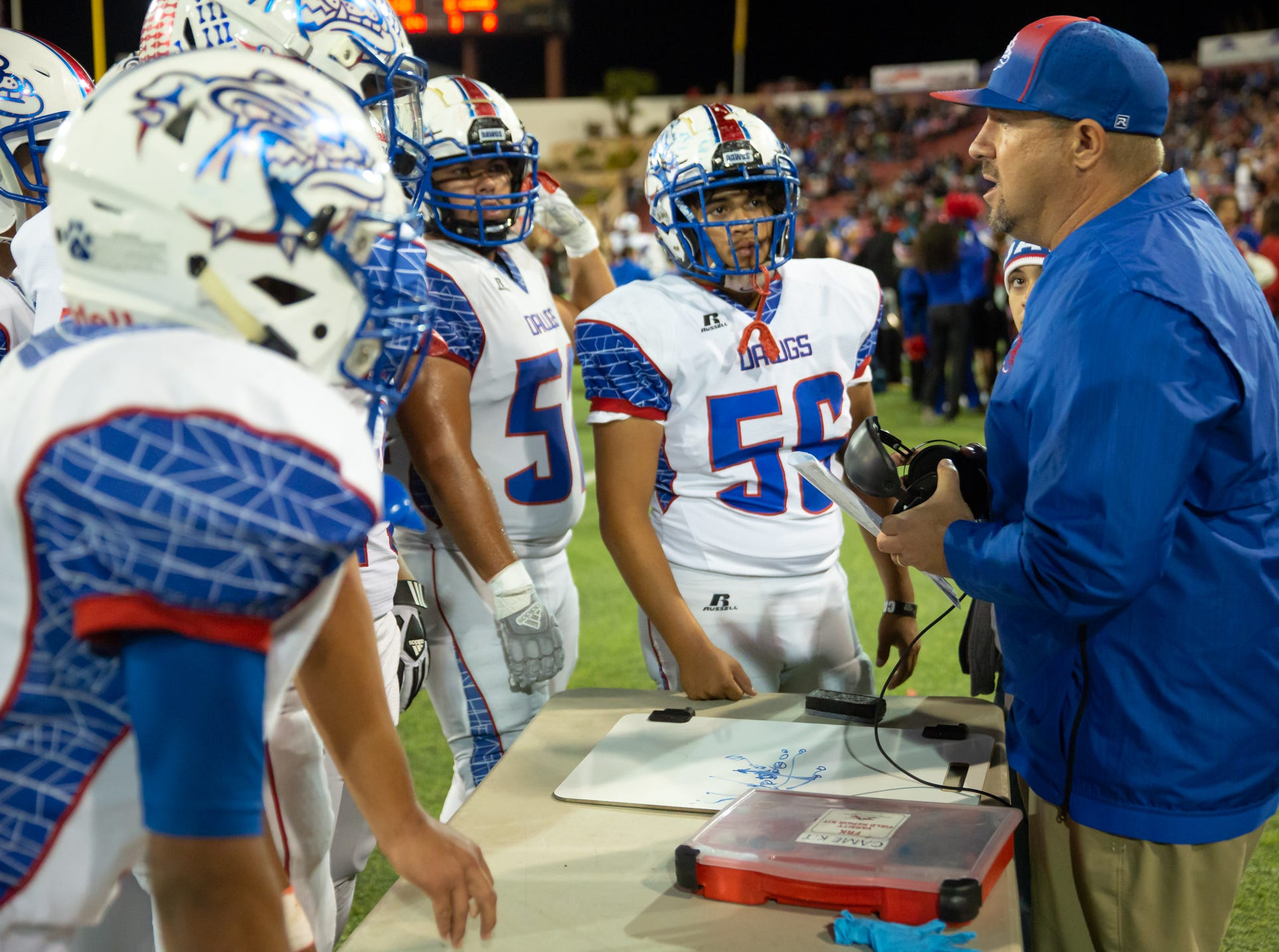 Las Cruces High School Head Football Coach Mark Lopez, works with his players on the sideline during the Cruces/Mayfield football game on Friday, Nov. 2, 2018, at Aggie Memorial Stadium.