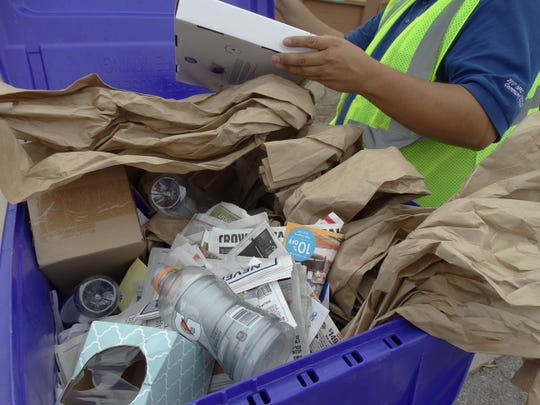 Arturo Ramos, SCSWA recycling attendant, inspects a curbside recycling bin to help educate residents about what is recyclable and what's not.