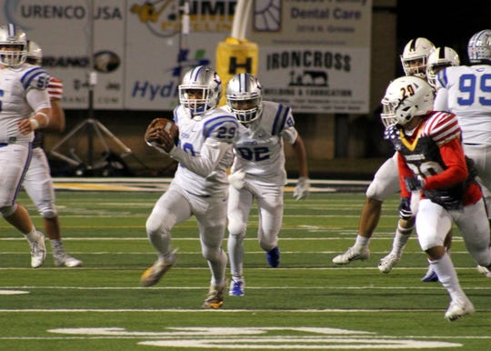 Juju Mathews runs for a big game during Friday's game against Hobbs. He ran three times for 57 yards and one touchdown in the first half.