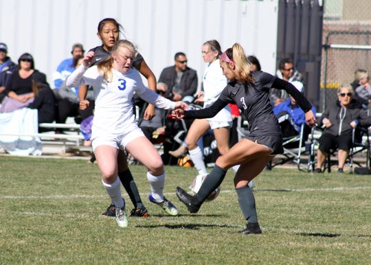 Carlsbad's Morgan Bradley (3) battles a Volcano Vista player for possession in the second half of Saturday's match.