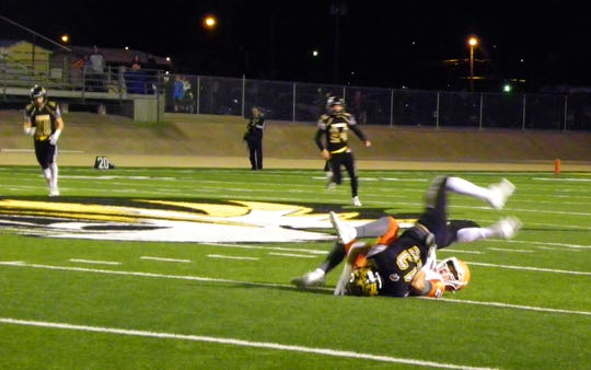 The Tigers' Julio Mendoza goes down hard fighting for the ball against Artesia.