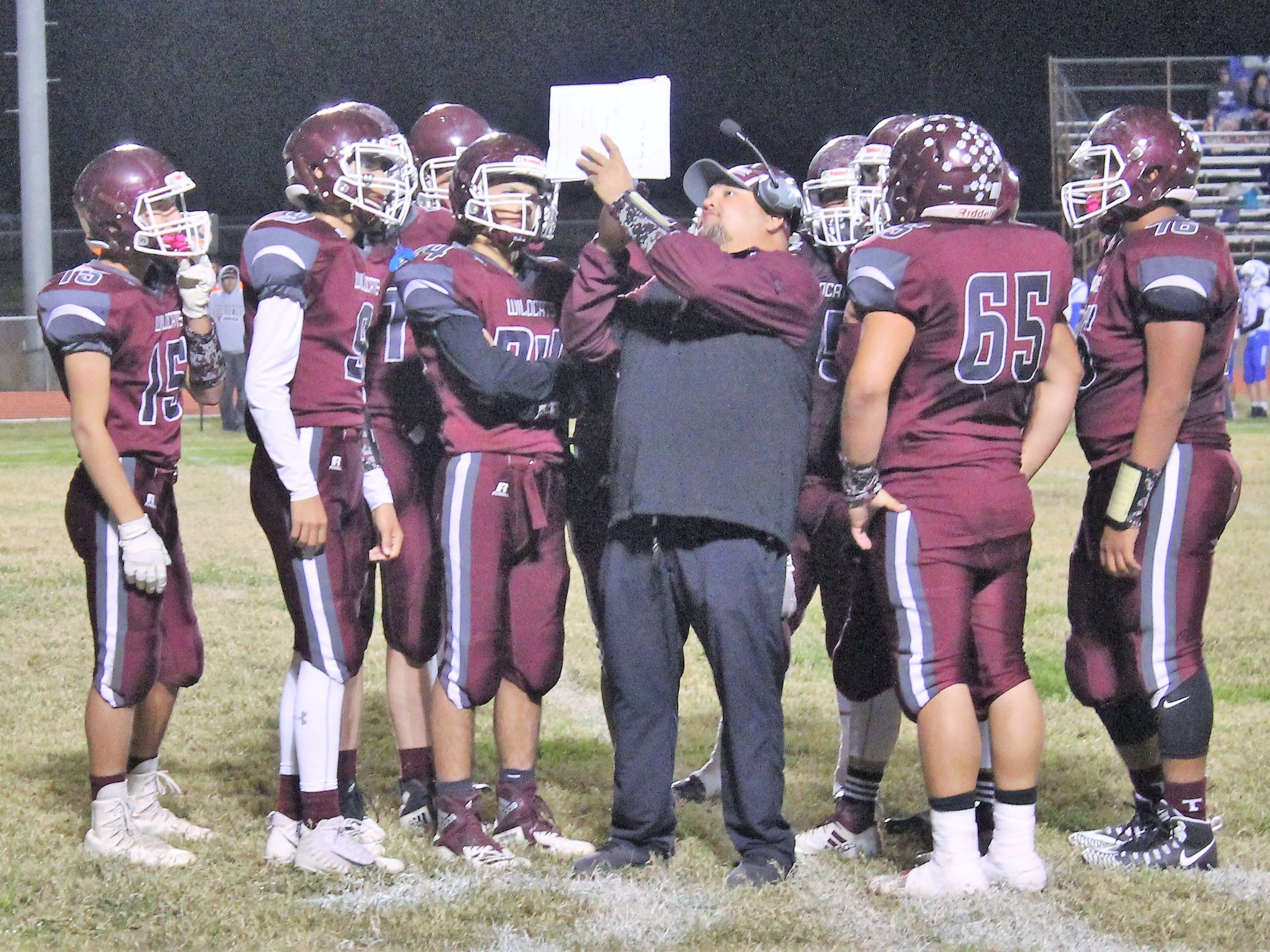 Tularosa Wildcats Assistant Coach Chance Coates reviews plays during a timeout at Friday night's game with the Dexter Demons.