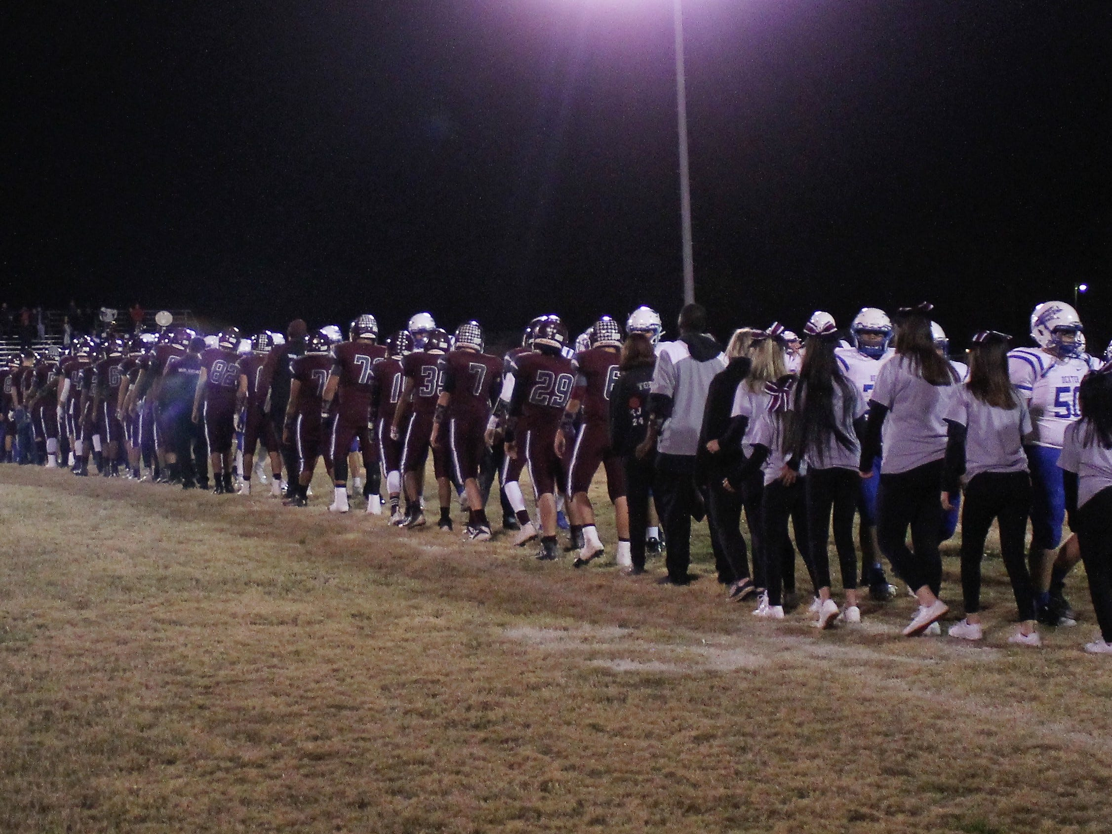 The Tularosa Wildcats and the Dexter Demons football teams, trainers, coaches and cheerleaders shake hands at the end of their game Friday night.