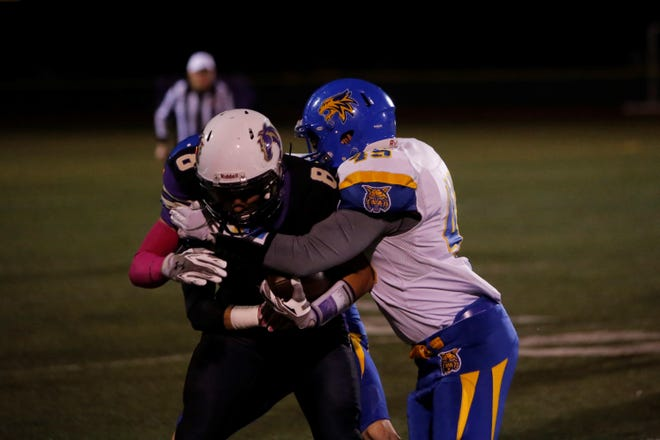 Kirtland Central's Brock Dowdy fights for extra yards against Bloomfield's Angelo Atencio (45) during a District 1-4A football game on Oct. 26 at KCHS. The Broncos earned a first-round bye in the 4A playoffs, while the Bobcats earned the No. 5 seed in 4A.