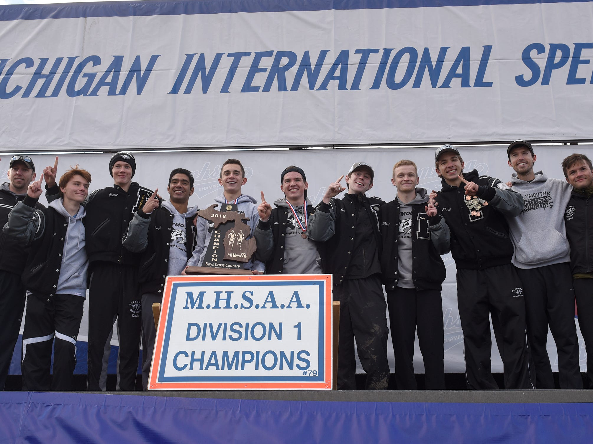Plymouth poses with the Division 1 teaam trophy at the 2018 cross country finals at Michigan International Speedway.