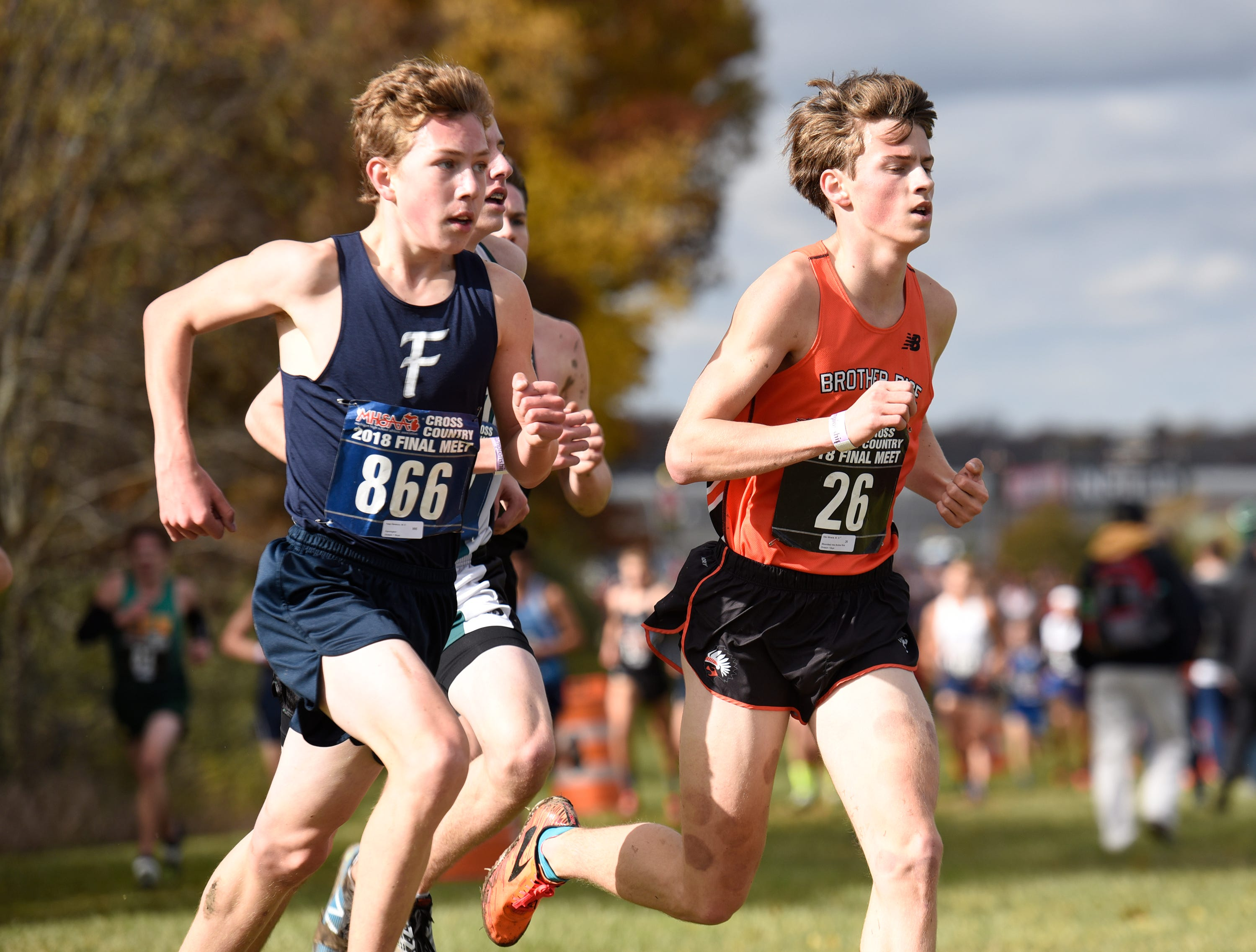 Farmington's Peter Baracco and Brother Rice runner Alec Miracle during the Division 1 2018 cross country finals at Michigan International Speedway.