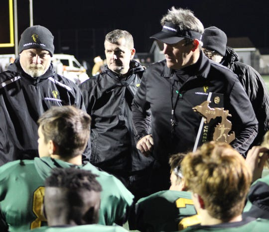 Veteran head coach Brendan Flaherty clutches the district championship while talking to his Groves squad following Friday's victory over Brother Rice.