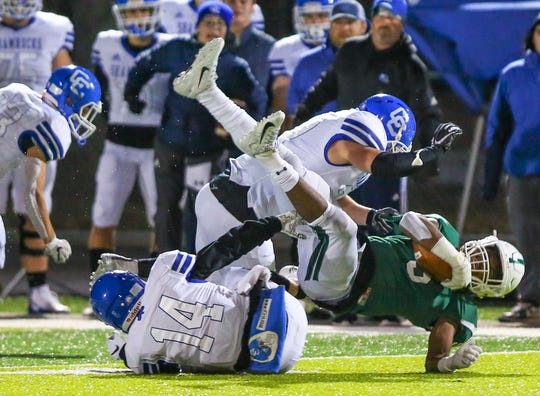 West Bloomfield's Lance Dixon (ball) gets upended by CC's Ryan Birney (14) and Brendin Yatooma (top).