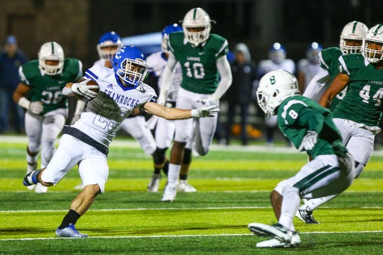 Catholic Central's Parker Bohland (with ball) tries to shake free from West Bloomfield tackler Makari Paige (8).