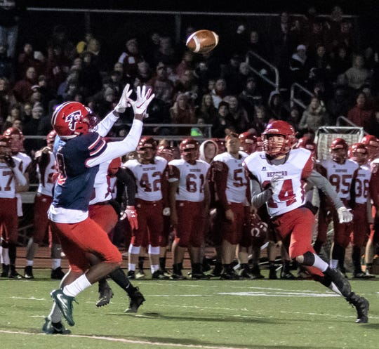 Franklin's Fredrick Biles (left) hauls in the pass against Temperance Bedford in the district championship.