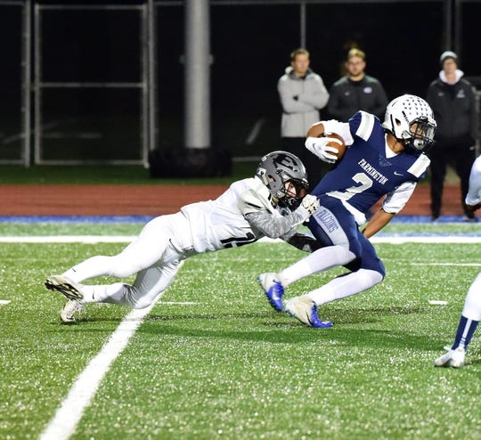 South Lyon East's Conner Turczyn (19) catches Farmington running back Keion Shaw (3) from behind.