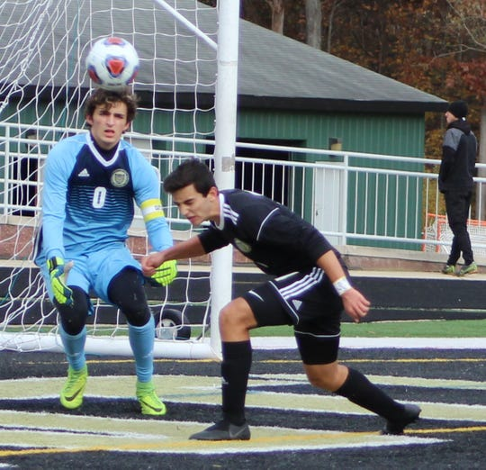 DCD's sophomore defender Tyler Foulk aids goalie Jon Dougherty by heading the ball away from the net during first-half action Saturday against Grand Rapids Forest Hills Northern.