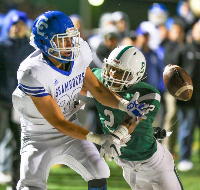 Catholic Central's Mike Harding (left) can't come up with the catch against West Bloomfield's D.J. Jenkins (2).