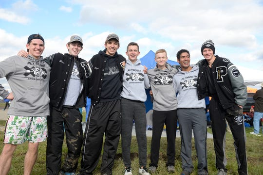 Plymouth runners pose after running and capturing the Division 1 title at the 2018 cross country finals at Michigan International Speedway.