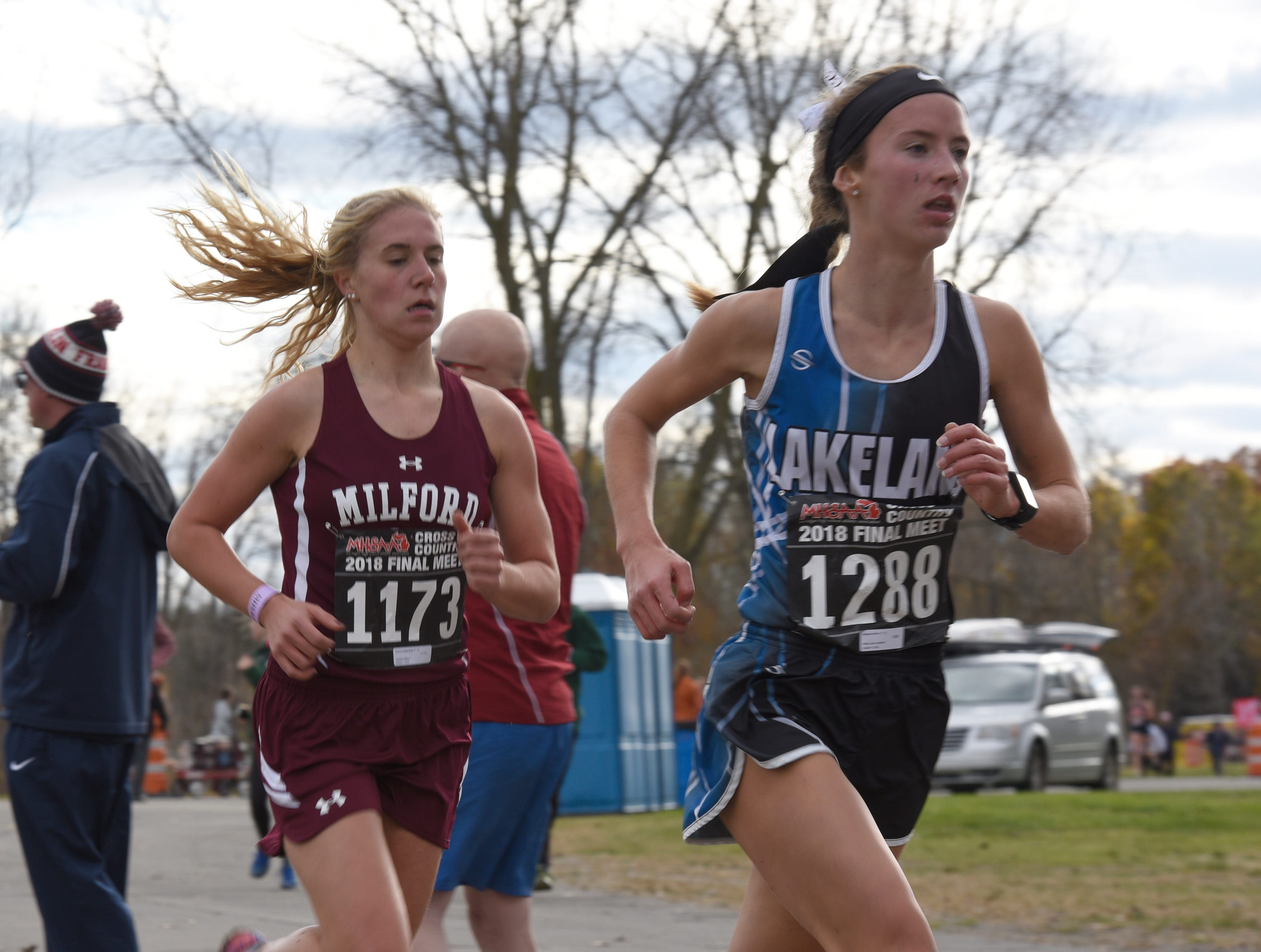 Lakeland's Madeline Rehm (1288) and Milford's Victoria Heiligenthal (1173) during the Division 1 2018 cross country finals at Michigan International Speedway.
