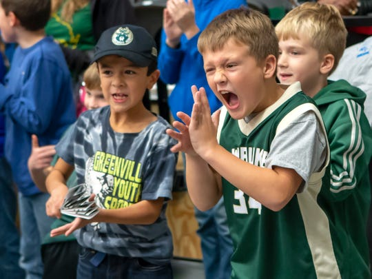Hayden Miller, left, with Immanuel Lutheran School of Greenville, cheers on the Wisconsin Herd as players run onto the court for a November 2018 game at Menominee Nation Arena in Oshkosh.