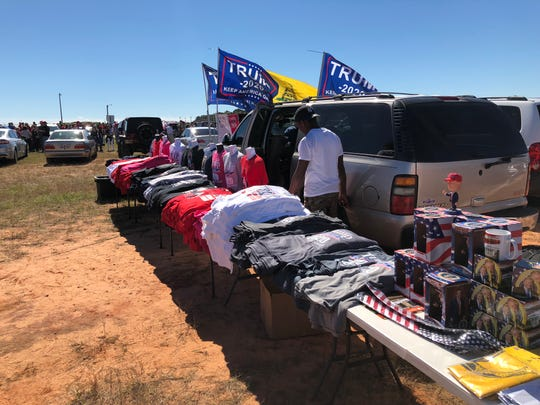 John Thompson sets up a table selling Trump gear outside of the Pensacola International Airport before President Donald Trump's rally on Saturday, Nov. 3, 2018.