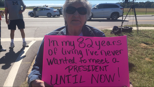 """Carolyn McBrayer holds a sign that reads """"In my 82 years of living I've never wanted to meet a president until now!"""" McBrayer and her daughter were among the supporters who gathered outside the Pensacola International Airport hours before President Donald Trump's rally on Saturday, Nov. 3, 2018."""