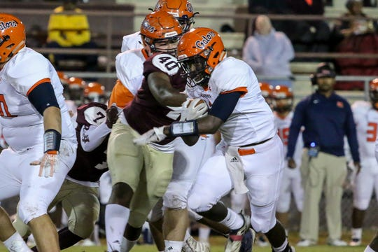 Escambia running back Frank Peasent (1) bounces off PHS defender James Kitt (40) and runs for additional yards in the last game of the regular season on Friday, November 2, 2018, at Pensacola High Schoool.
