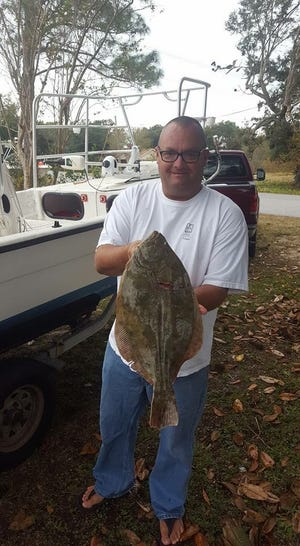 Local angler Charlie Trinque with a nice flounder he gigged along the Pensacola Bay side of Fort Pickens.