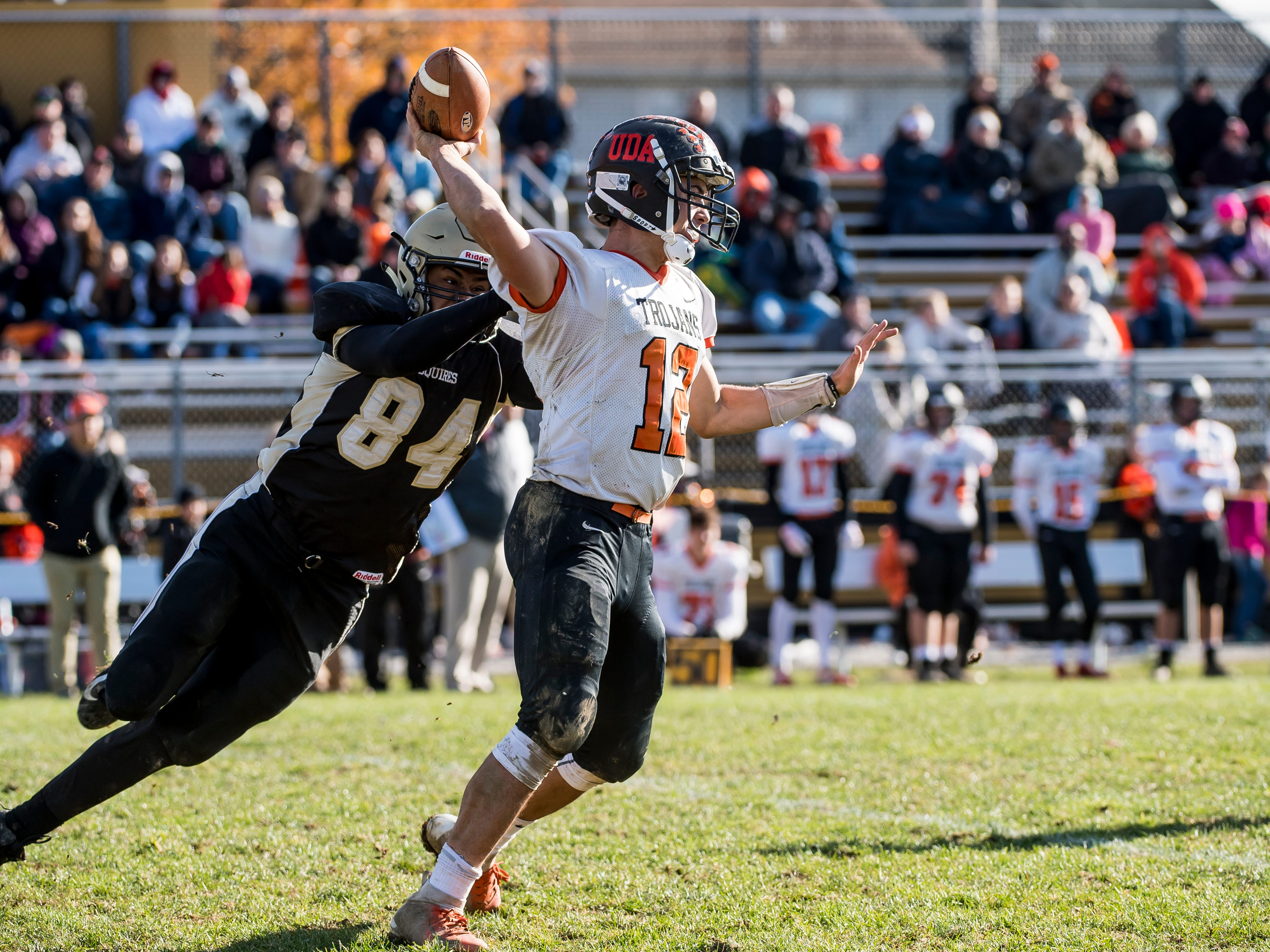 Delone Catholic's Marquis Suite (84) hits Macklin Ayers as he throws the ball during a District III Class 2A semifinal game on Saturday, November 3, 2018. The Squires won 48-23.