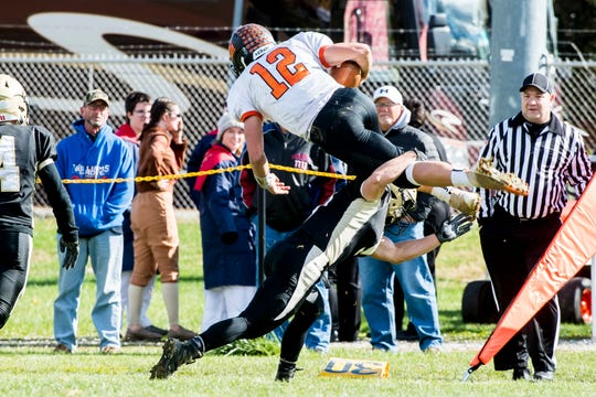 Delone Catholic's Logan Brown tackles Upper Dauphin's Macklin Ayers (12) during a District III Class 2A semifinal game against Upper Dauphin on Saturday, November 3, 2018. The Squires won 48-23.
