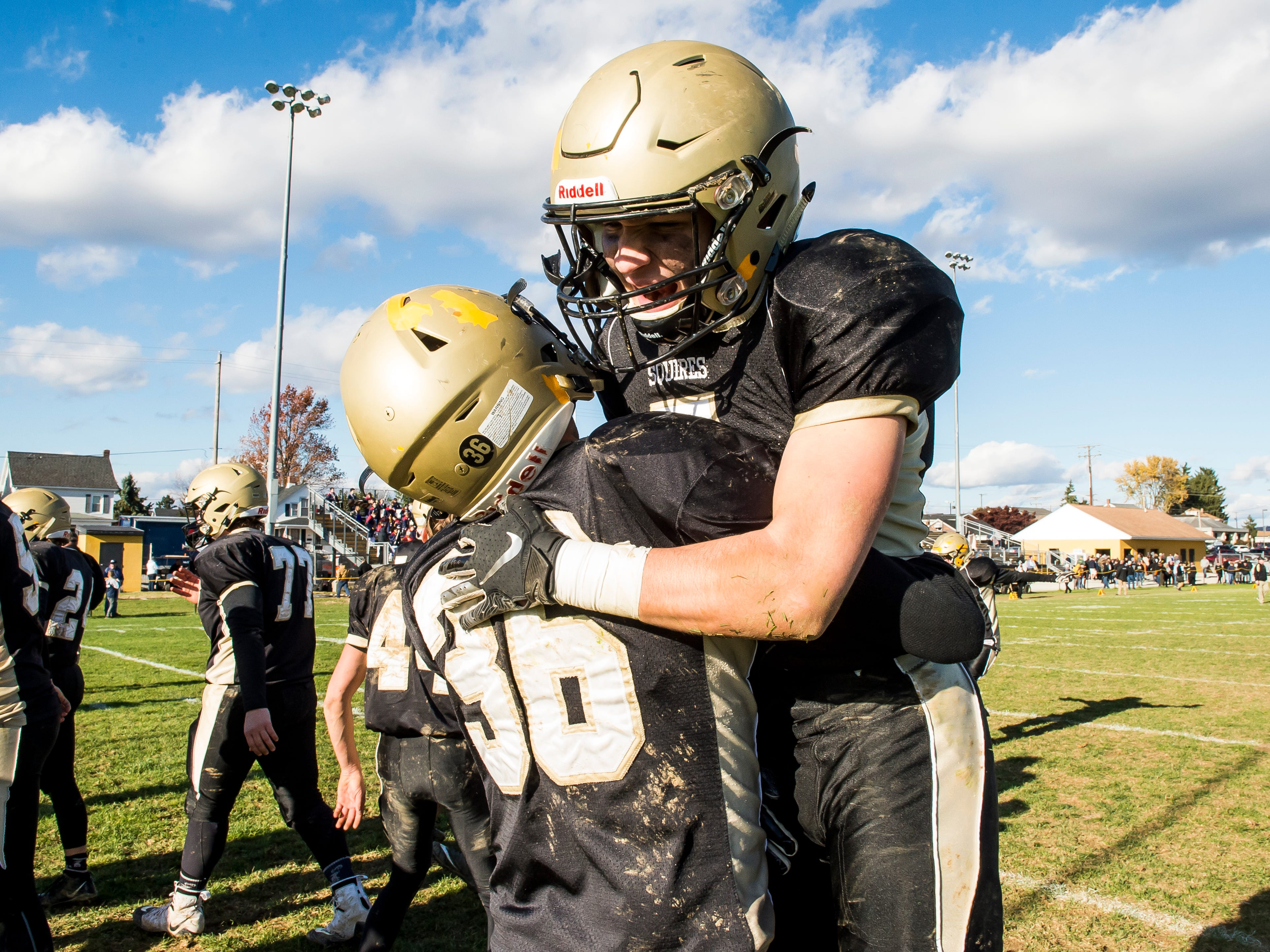 Delone Catholic's Ryan Myers (36) celebrates with Gabe Lee after the Squires defeated Upper Dauphin 48-23 in a District III Class 2A semifinal game on Saturday, November 3, 2018.