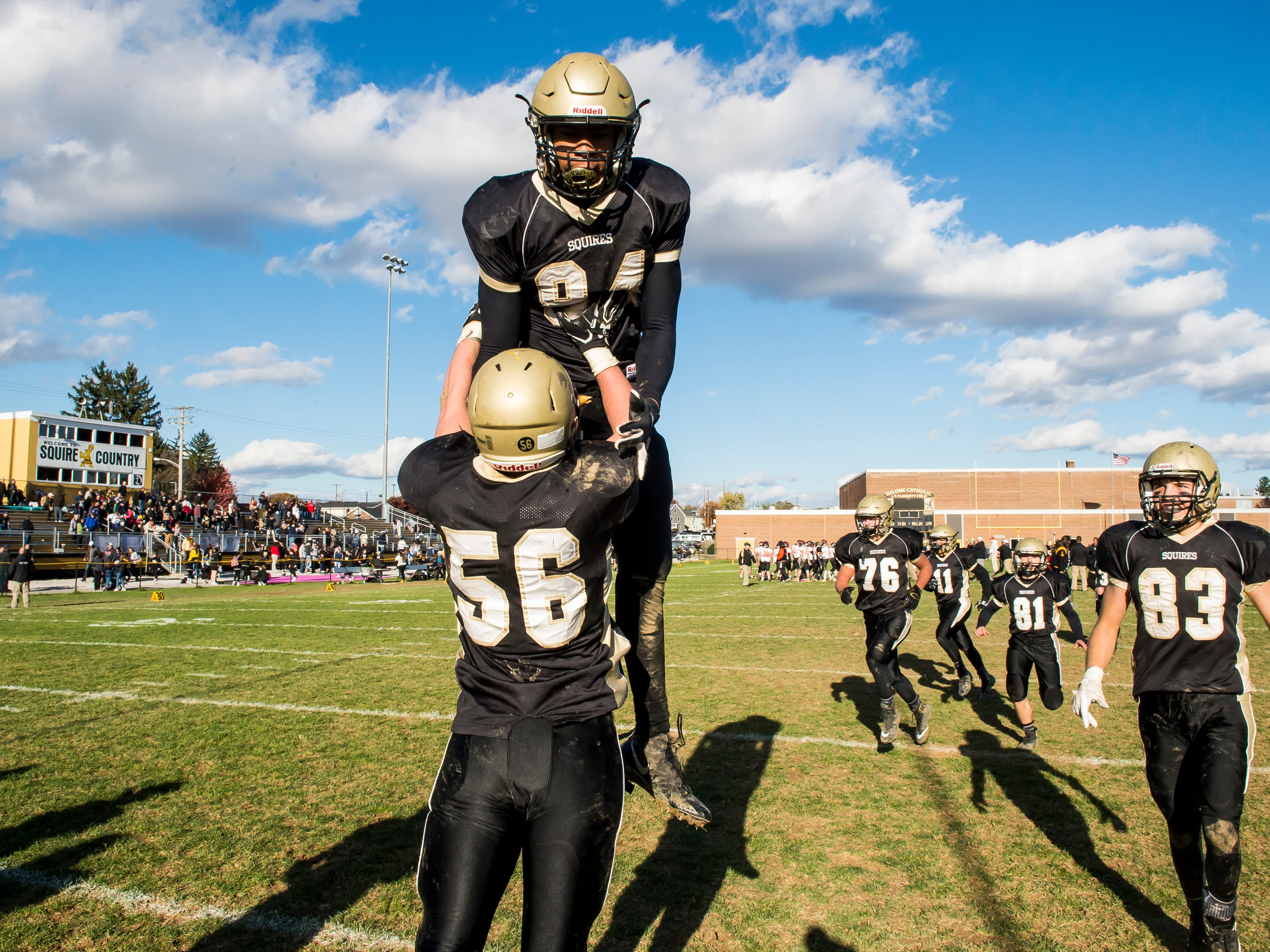 Delone Catholic's Marquis Suite (84) and Sean Kronner (56) celebrate after defeating Upper Dauphin 48-23 in a District III Class 2A semifinal game on Saturday, November 3, 2018. The Squires will play in the District title game against York Catholic on Friday.