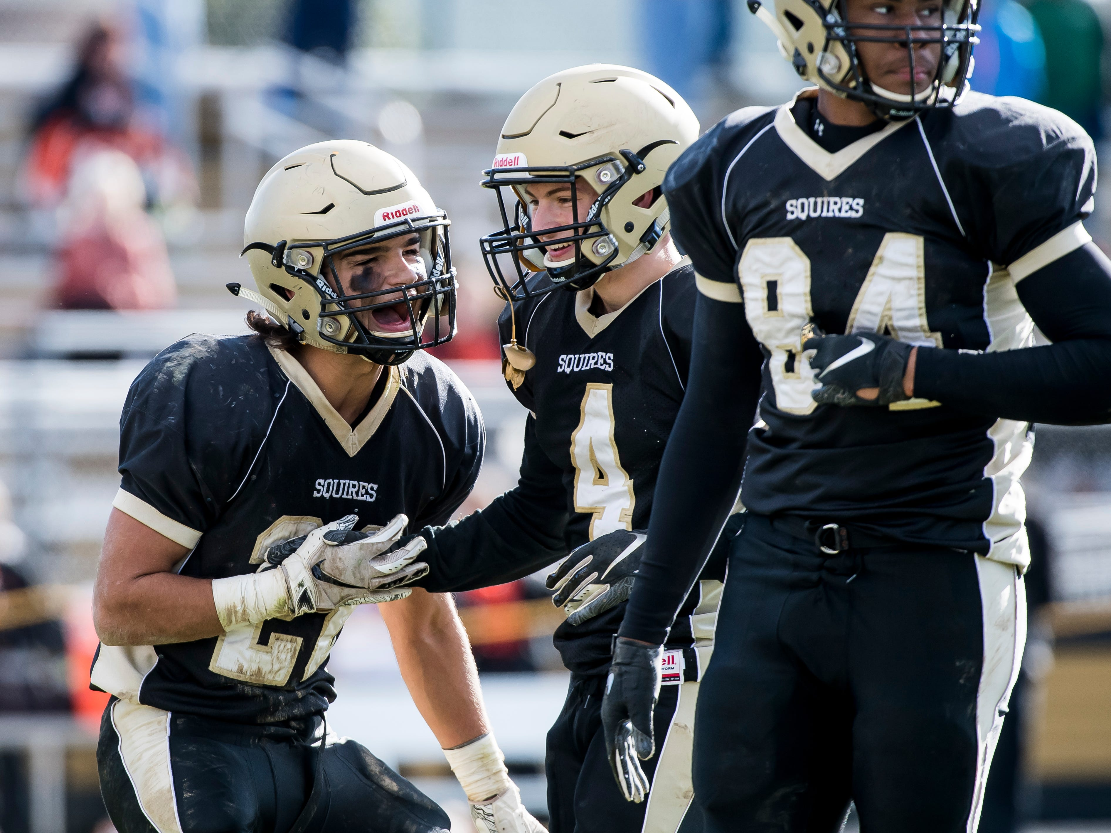 Delone Catholic's Joe Hernandez (left) pumps up Colin Gebhart (4) after Gebhart delivered a big tackle during a District III Class 2A semifinal game against Upper Dauphin on Saturday, November 3, 2018. The Squires won 48-23.