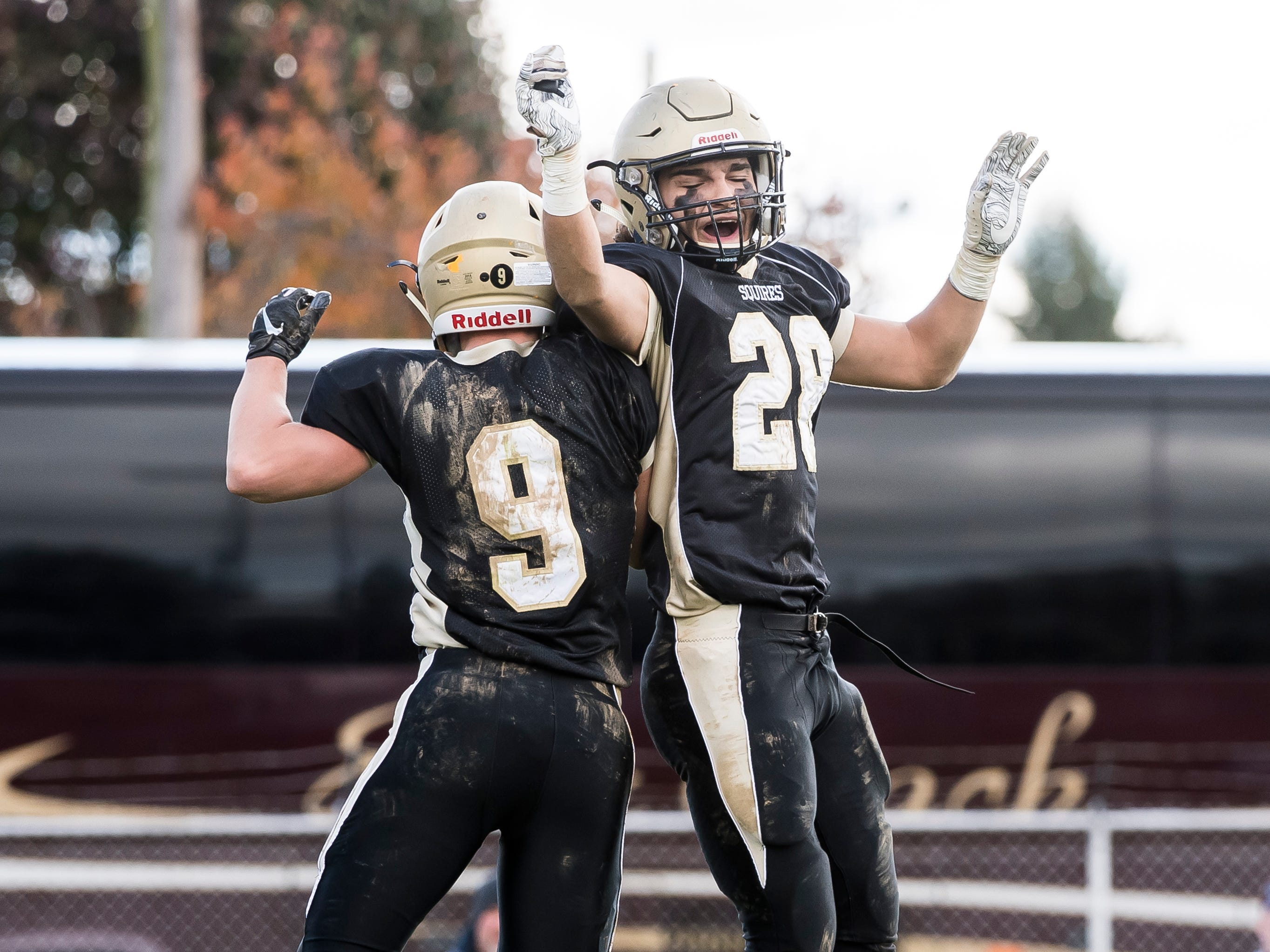 Delone Catholic's Logan Brown (9) celebrates with Joe Hernandez (28) after scoring a touchdown against Upper Dauphin in a District III Class 2A semifinal game on Saturday, November 3, 2018. The Squires won 48-23.