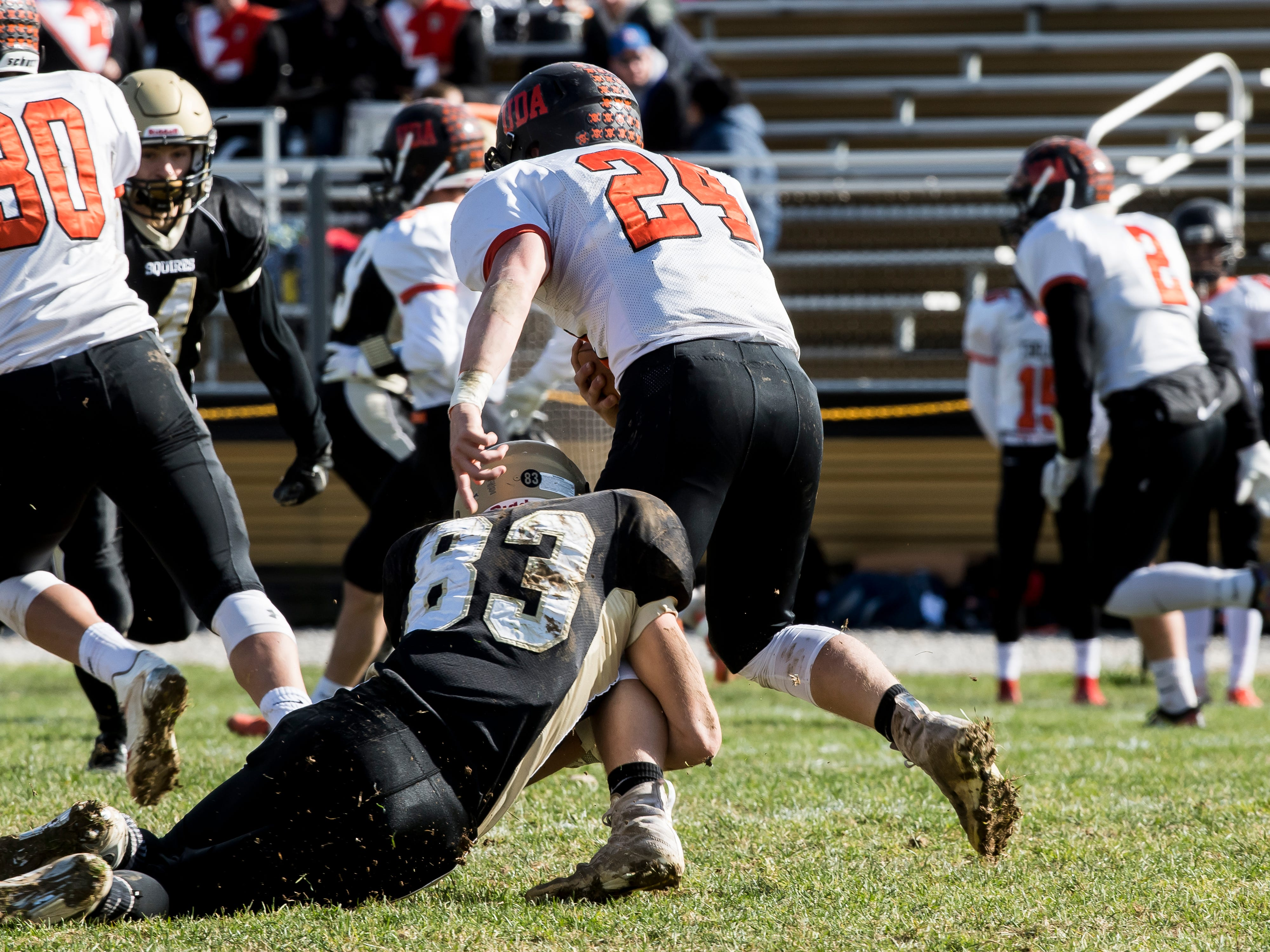 Delone Catholic's Gabe Hernandez (83) tackles Upper Dauphin's Jake Ramberger (24) during a District III Class 2A semifinal game on Saturday, November 3, 2018. The Squires won 48-23.