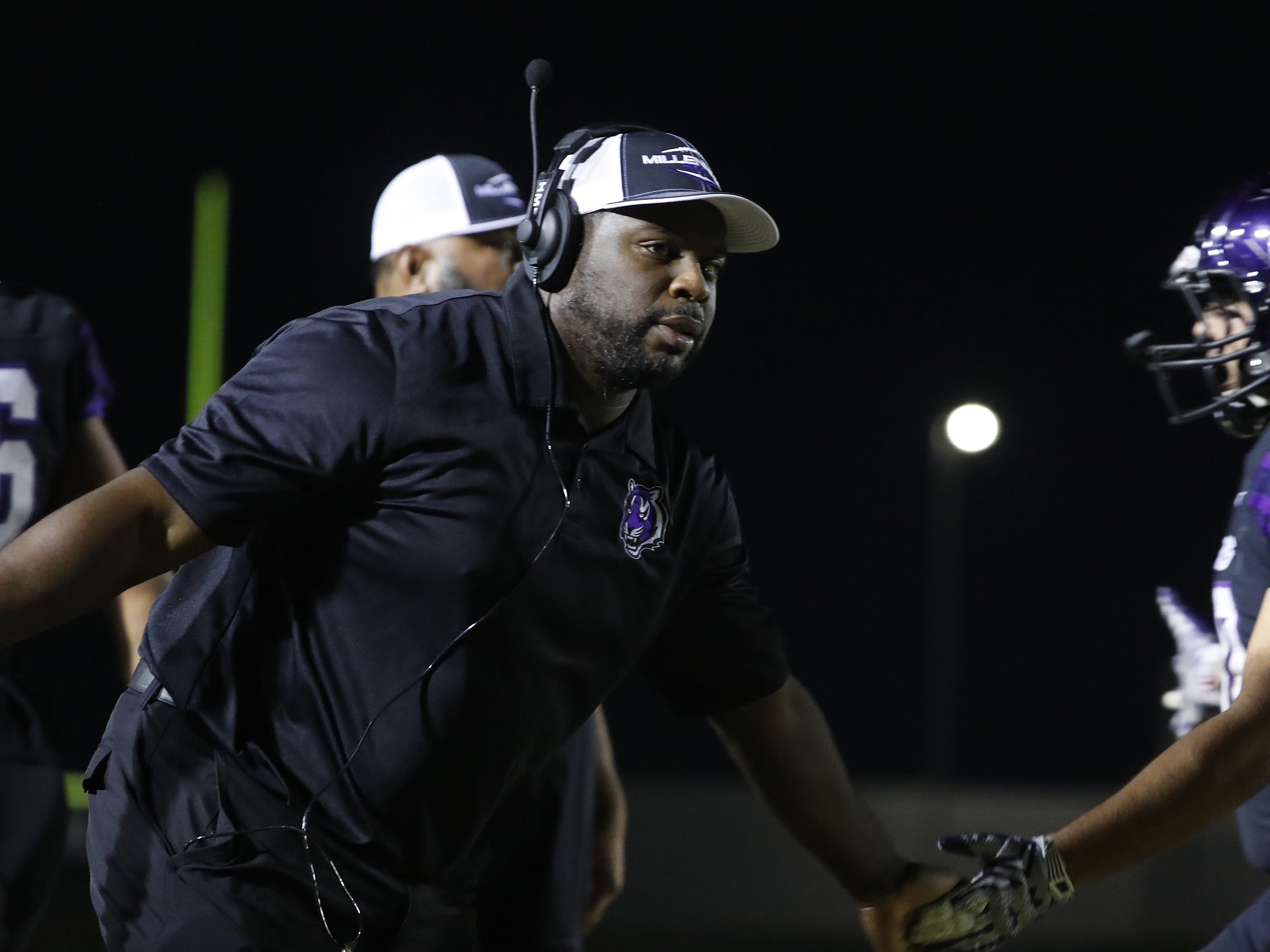 Millennium's head coach Lamar Early high-fives his team during the first round of the AIA State Football Playoffs against Flowing Wells at Millennium High School in Goodyear, Ariz. on Nov. 2, 2018.