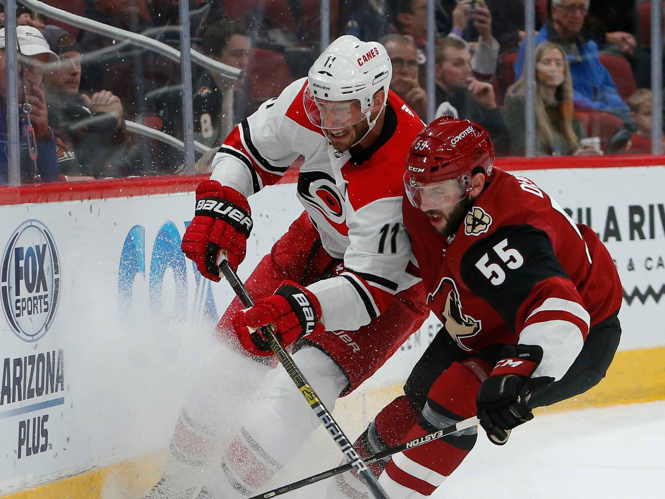 Carolina Hurricanes center Jordan Staal (11) and Arizona Coyotes defenseman Jason Demers vie for the puck during the first period of an NHL hockey game Friday, Nov. 2, 2018, in Glendale, Ariz. (AP Photo/Rick Scuteri)