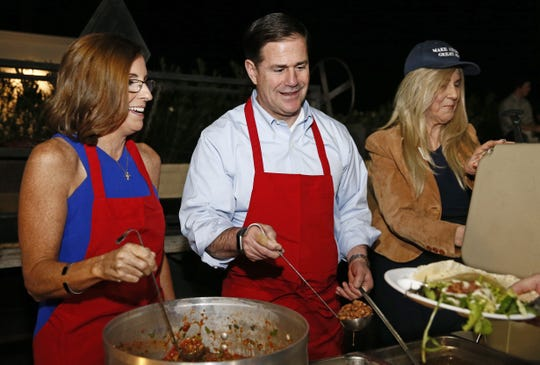 Martha McSally, the Republican candidate for the U.S. Senate, and Gov. Doug Ducey serve-up the beans and salsa at a get-out-the-vote event on Nov. 2, 2018, in Phoenix.