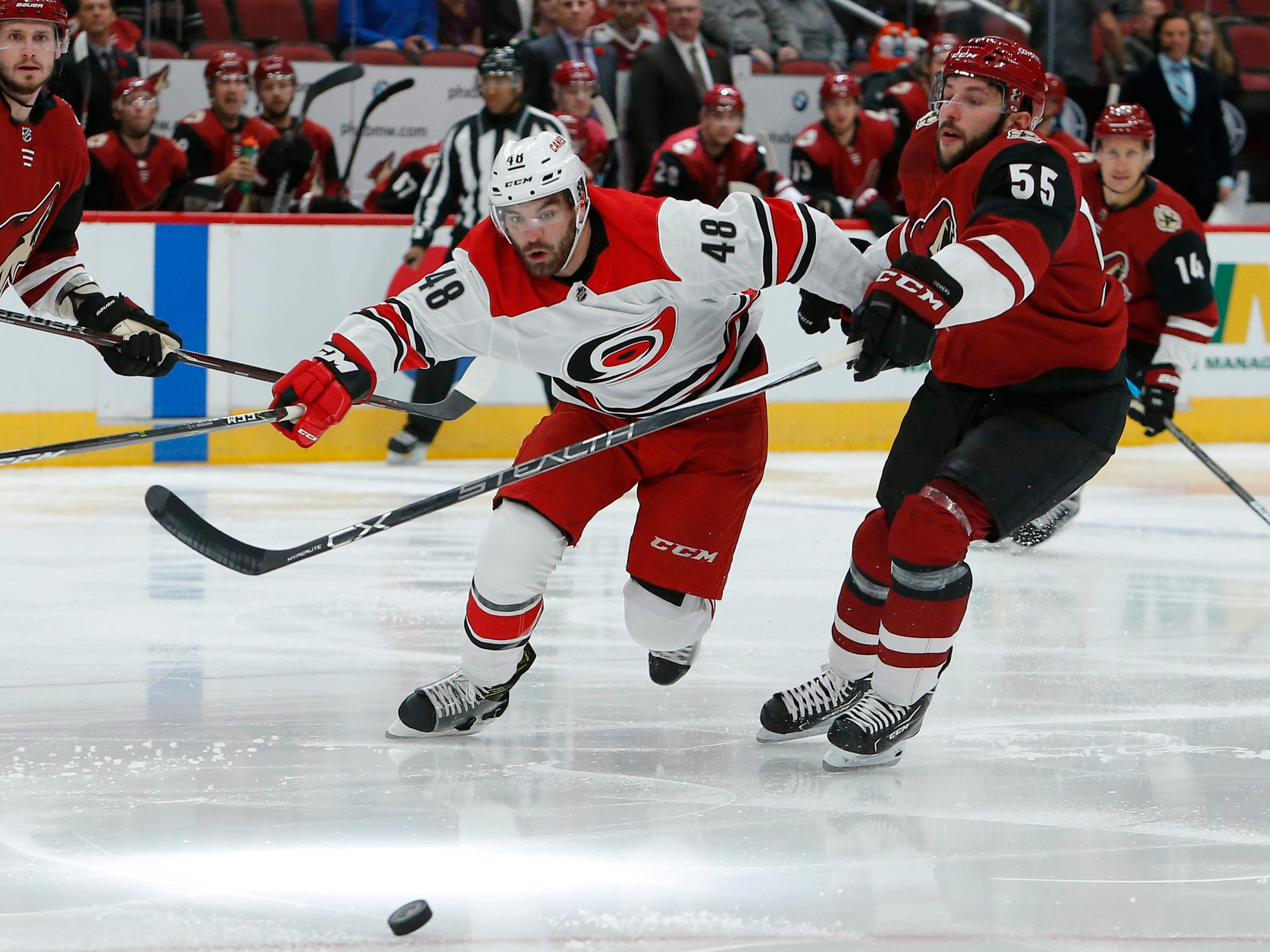 Carolina Hurricanes left wing Jordan Martinook (48) battles for the puck with Arizona Coyotes defenseman Jason Demers during the first period of an NHL hockey game Friday, Nov. 2, 2018, in Glendale, Ariz. (AP Photo/Rick Scuteri)