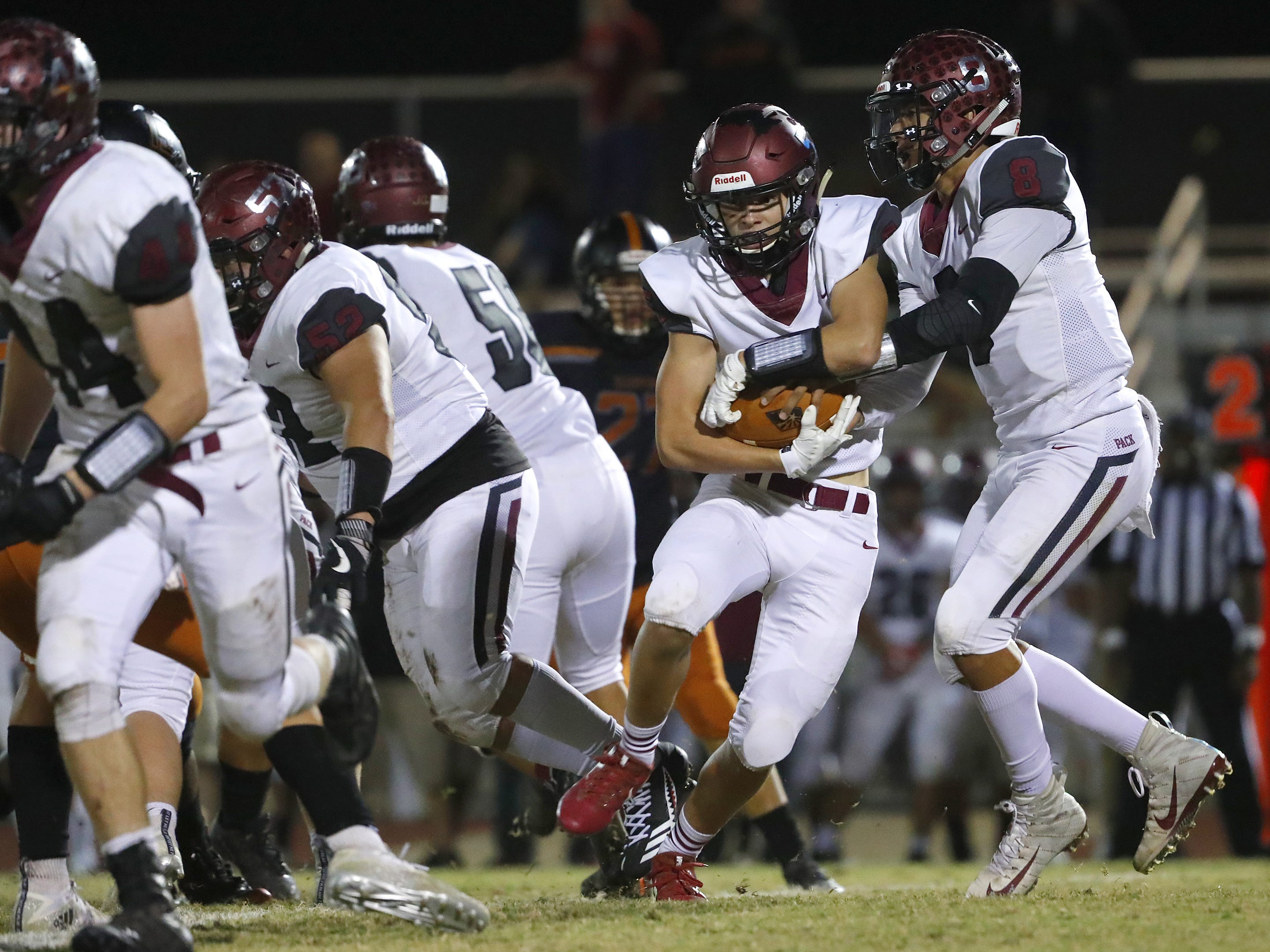 Walden Grove's Alex Lopez (8) hands the ball off to William Fortin (5) against Desert Edge during the first round of the AIA State Football Playoffs at Desert Edge High School in Goodyear, Ariz. on Nov. 2, 2018.