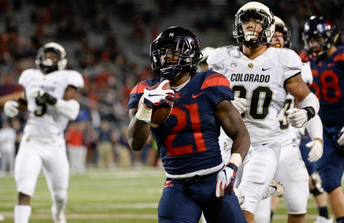 Nov 2, 2018; Tucson, AZ, USA; Arizona Wildcats running back J.J. Taylor (21) runs the ball under pressure from Colorado Buffaloes linebacker Drew Lewis (20) during the first half at Arizona Stadium.