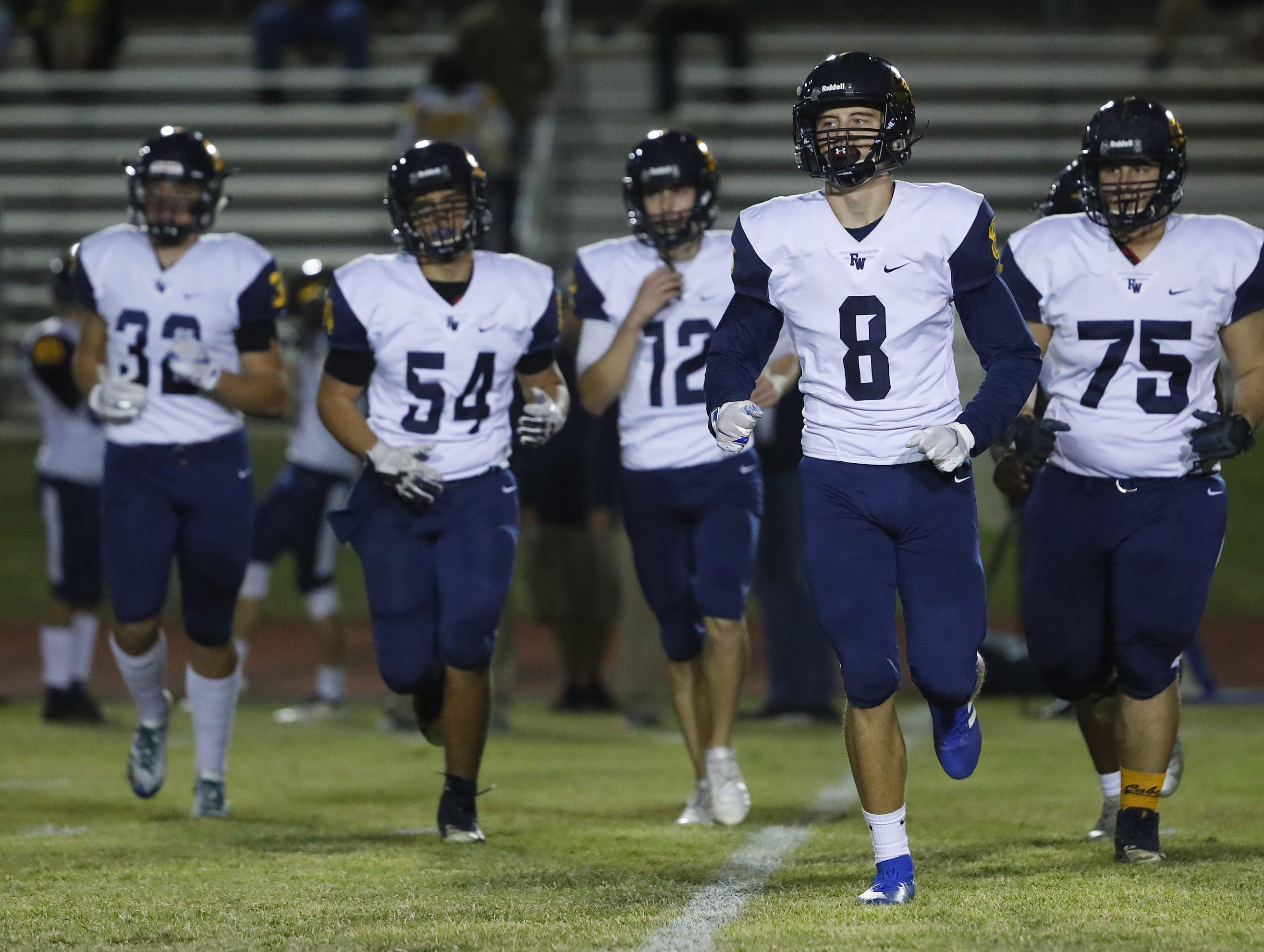 Flowing Wells' Lloyd Love (8) and his teammates take the field to play Millennium during the first round of the AIA State Football Playoffs at Millennium High School in Goodyear, Ariz. on Nov. 2, 2018.