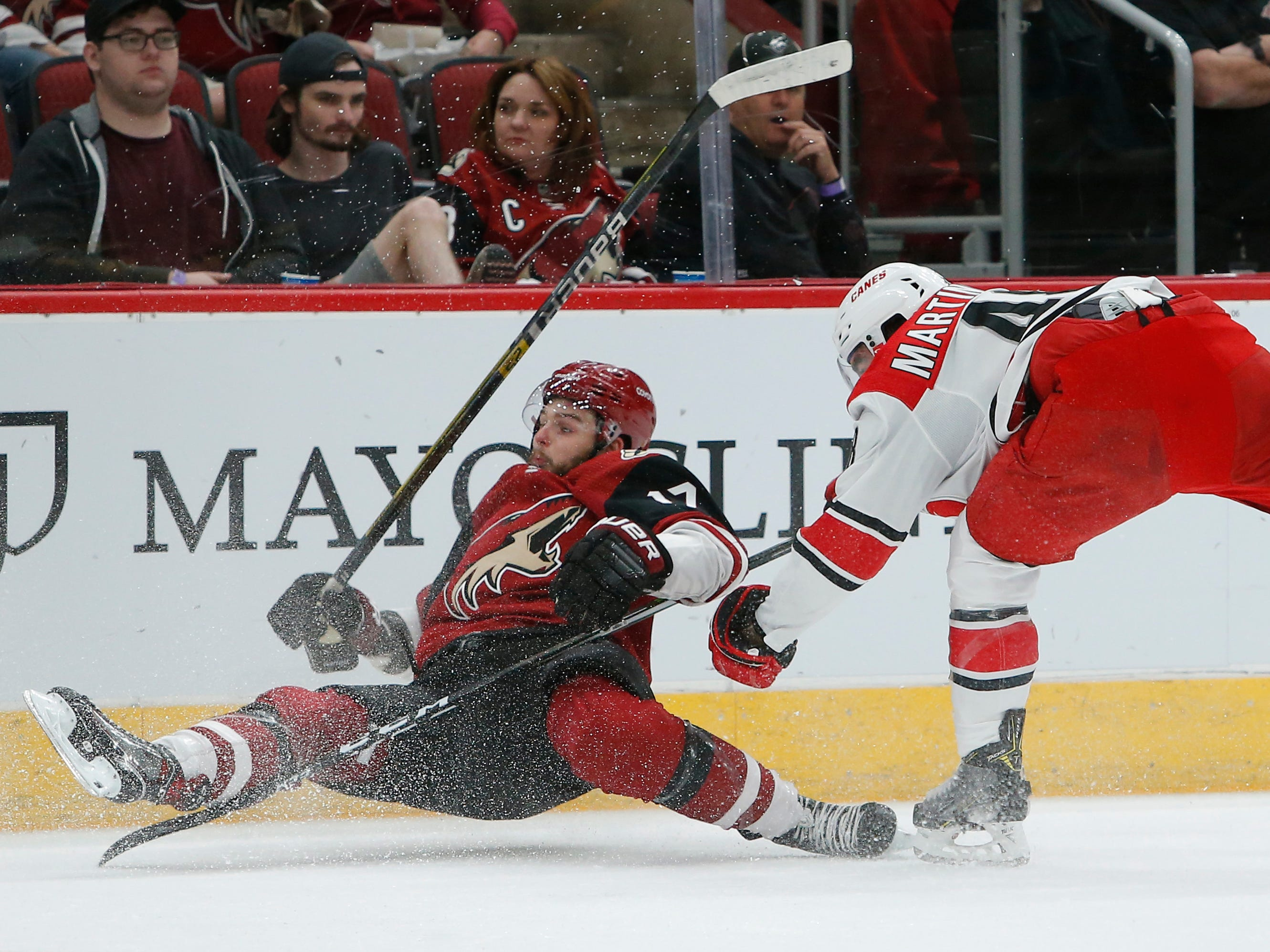 Carolina Hurricanes left wing Jordan Martinook (48) drags down Arizona Coyotes center Alex Galchenyuk for a tripping penalty in the first period during an NHL hockey game, Friday, Nov. 2, 2018, in Glendale, Ariz. (AP Photo/Rick Scuteri)