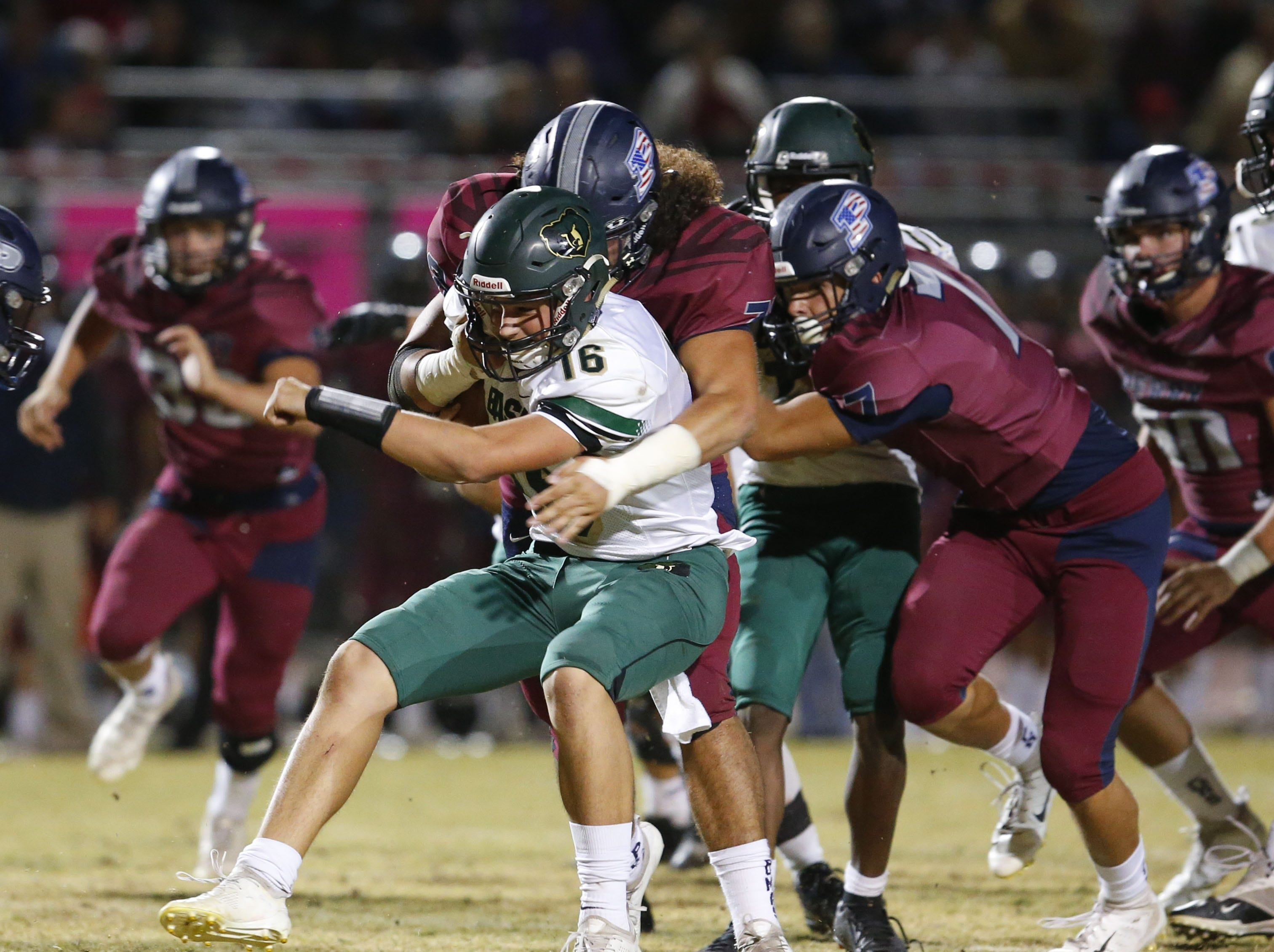 Basha's quarterback Gabe Friend (16) is stopped by Perry Michael Warnick (78) left, and Perry Andrew Moon (7) during a scramble in football game at Perry High School on Nov. 2. #azhsfb